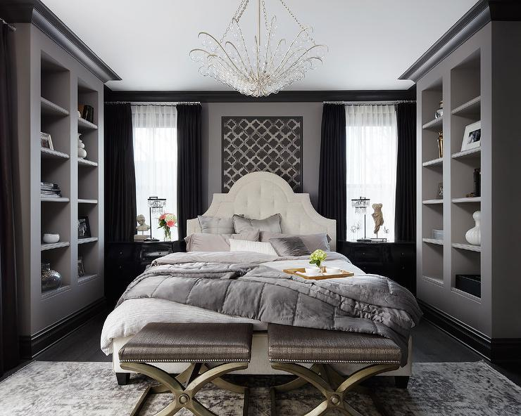 suzann kletzien chic bedroom features a white tufted bed dressed in gray shams and quilt flanked by glossy black nightstands adorned with gold knobs and