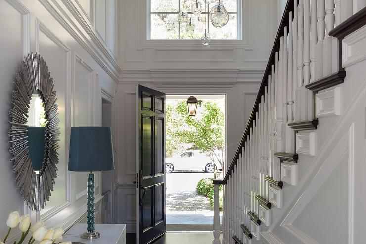 Long Foyer Boasts Walls Clad In Decorative Moldings Lined With A White  Waterfall Console Table Under A Silver Sunburst Mirror Facing A Staircase  Wall.