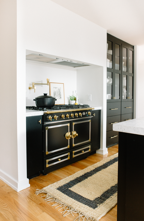 and black kitchen features an alcove filled with a black and gold