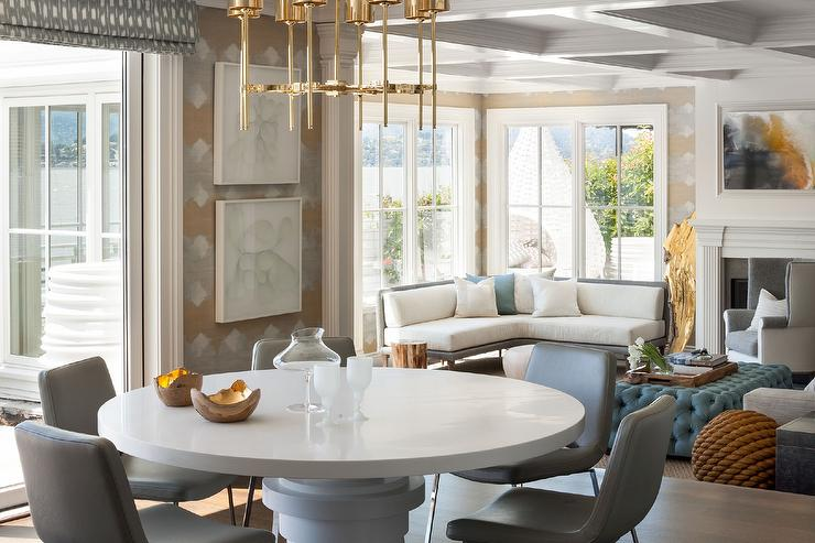 Contemporary Dining Room Boasts A Brass Chandelier Illuminating Round White Lacquered Table Lined With Gray Leather Chairs Facing Sunken
