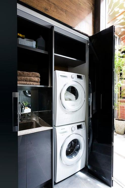 Glossy Black Double Doors Open To A Closet Filled With White Stacked Washer And Dryer Next Cabinets Fitted Sink Under Shelves