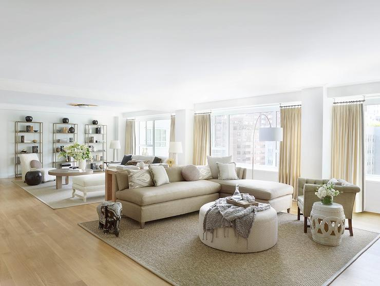 view full size long open living room features a tan armless sofa with chaise lounge facing a white round ottoman