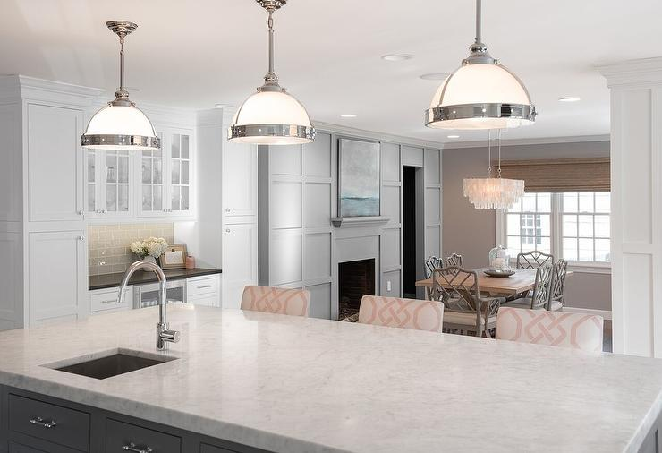 Beautiful Kitchen Features A Dark Gray Center Island Topped With White  Marble Fitted With A Small Prep Sink And A Gooseneck Faucet Lined With  Three Pink ...