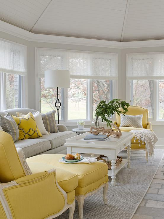 Round Sunroom With Gray Roll Arm Sofa And Yellow Bergere Chairs