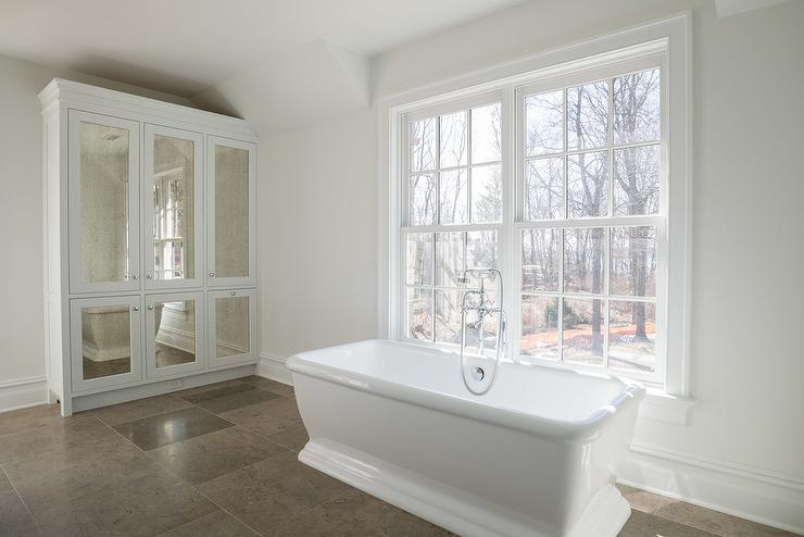 White Bathroom Features A Freestanding Tub Placed Under A Window Situated  Across From A Tall Antiqued Mirrored Linen Cabinet.