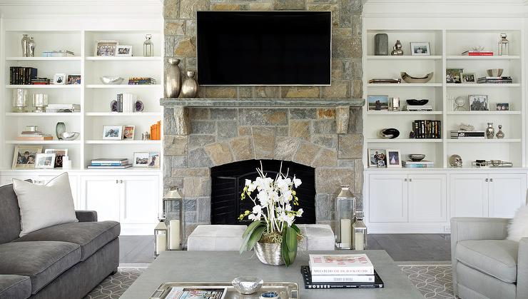 Chic cottage living room features a stone fireplace accented with a wood mantle under art next to built in shelves and cabinets lined with a flat panel tv illuminated by Schoolhouse Electric Princeton Sconces.