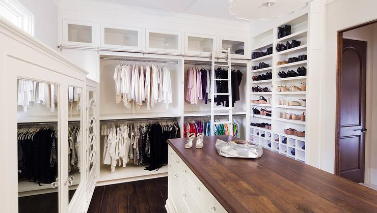 Chic Walk In Closet Features Stacked Clothes Rails Lined With A Ladder On  Rails Adjacent To A Wall Lined With Floor To Ceiling Shoe Shelves And  Cubbies.