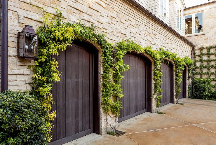 dark stained garage doors covered in ivy view full size