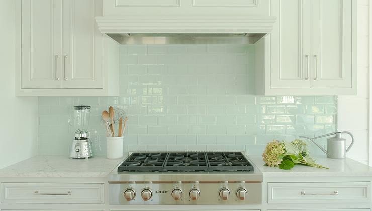 white kitchen cabinets with blue glass tile backsplash