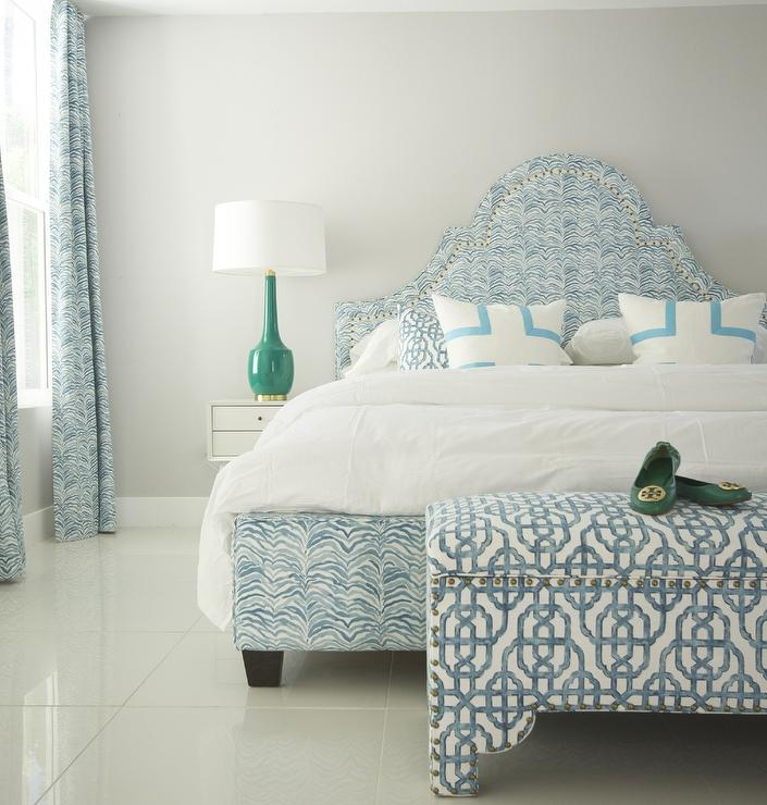 blue bedroom features a blue bed with curved headboard upholstered in serengeti seaside fabric lined with white and blue pillows next to a white nightstand
