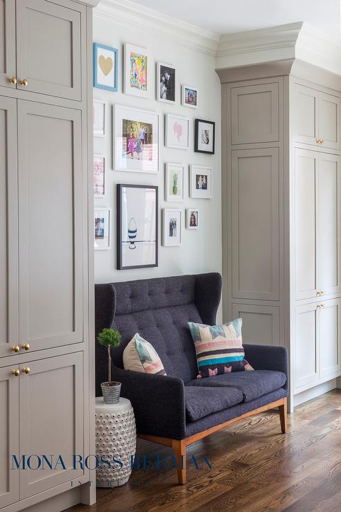 Gray Wingback Settee Flanked By Floor To Ceiling Gray Cabinets