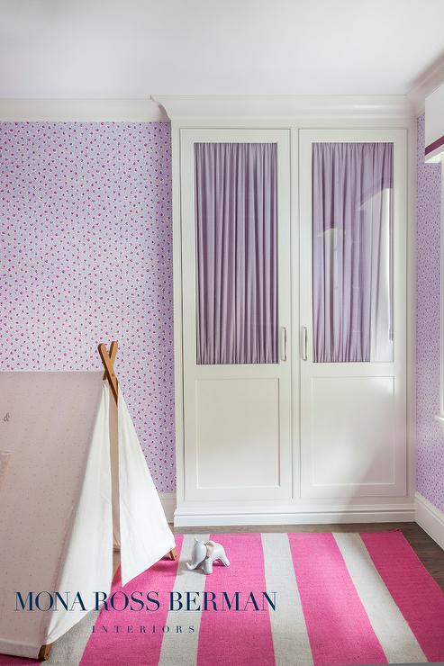 Purple and pink girl's bedroom features walls clad in purple floral  wallpaper lined with a tall built-in wardrobe cabinet with glass doors  lined with purple ...