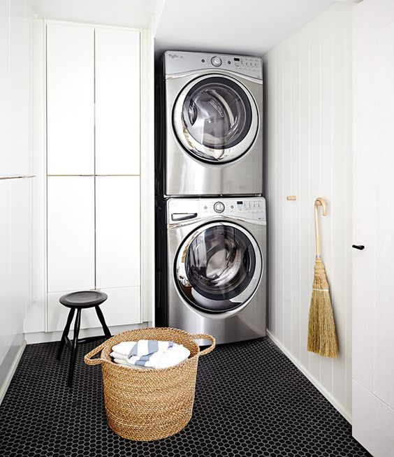 Fantastic laundry room features a silver stacked washer and dryer placed  next to floor to ceiling cabinets alongside a black hex tiled floor. Gray Laundry Room with Black and Gray Hex Floor Tiles
