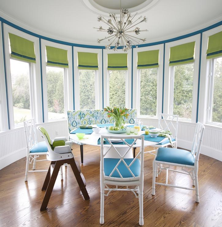 Contemporary Round Dining Room Is Filled With A Modern White Table Lined Blue And Green Upholstered Bench Faux Bamboo