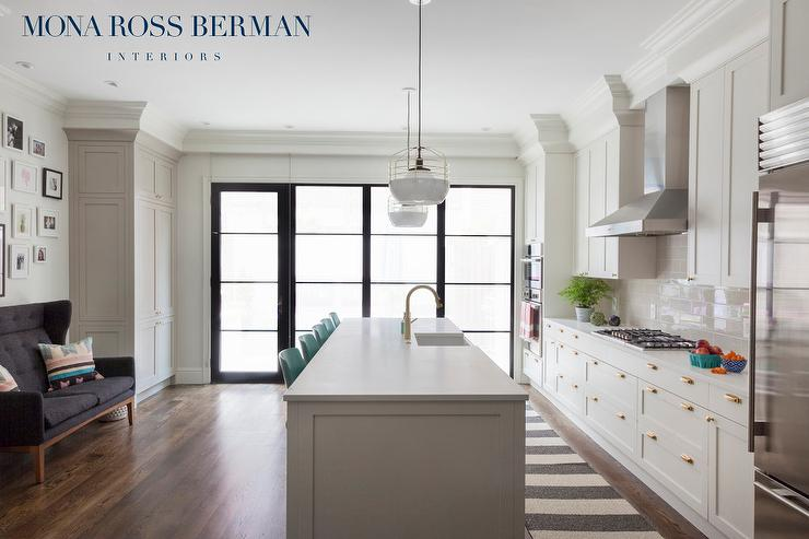 White Kitchen Cabinets With Brass Cup Pulls And Gray Tile