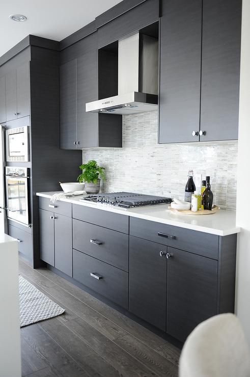 Dark gray flat front kitchen cabinets with gray mosaic for Flat black kitchen cabinets