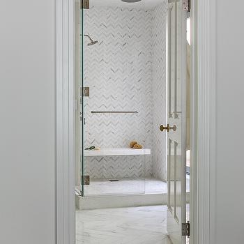 walk in shower with white and gray herringbone tiles and floating shower bench