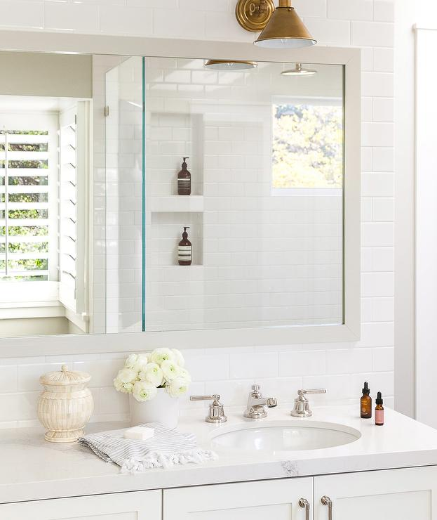 Brass bathroom sconce design ideas white master bathroom features a white washstand topped with white quartz under a white framed mirror lining a subway tiled wall illuminated by an aged aloadofball Images