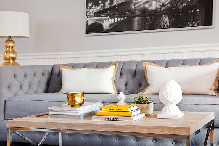 Chic Living Room Features A Gray Tufted Sofa Lined With Gold Border Shams Flanked By End Tables And Triple Gourd Lamps Facing Wood Metal Coffee