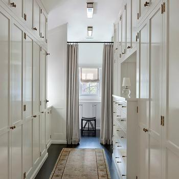 Long And Narrow Walk In Closet With Floor To Ceiling Cabinets