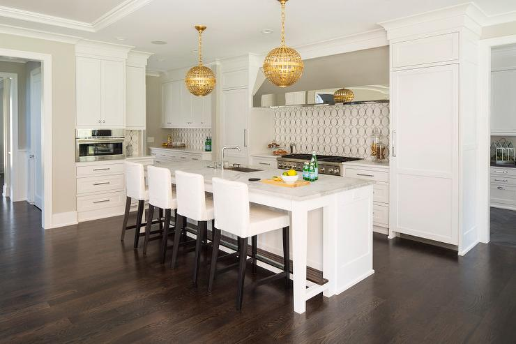 White Kitchen Island With Gold Globe Pendants