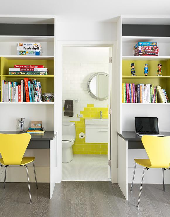 gray kids desk under yellow shelves with yellow chairs