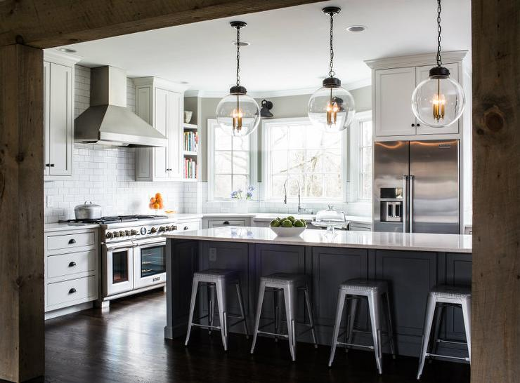 White and gray kitchen features white cabinets adorned with bronze cup