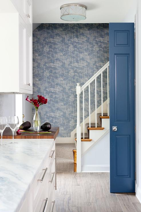 Blue Foyer Boasts A Staircase Wall Clad In Gray And Blue Textured Wallpaper  Next To A Small Closet Finished With A Blue Closet Door.