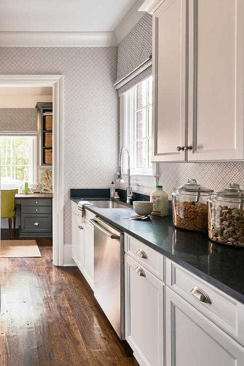 Long kitchen pantry features white shaker cabinets adorned with satin