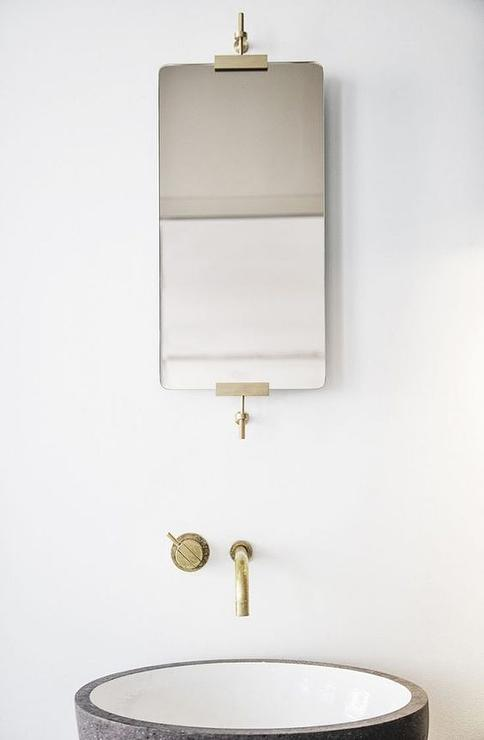 chic minimalist bathroom boasts a sleek mirror with brass trim over an aged brass wall mount faucet and a round sink bowl