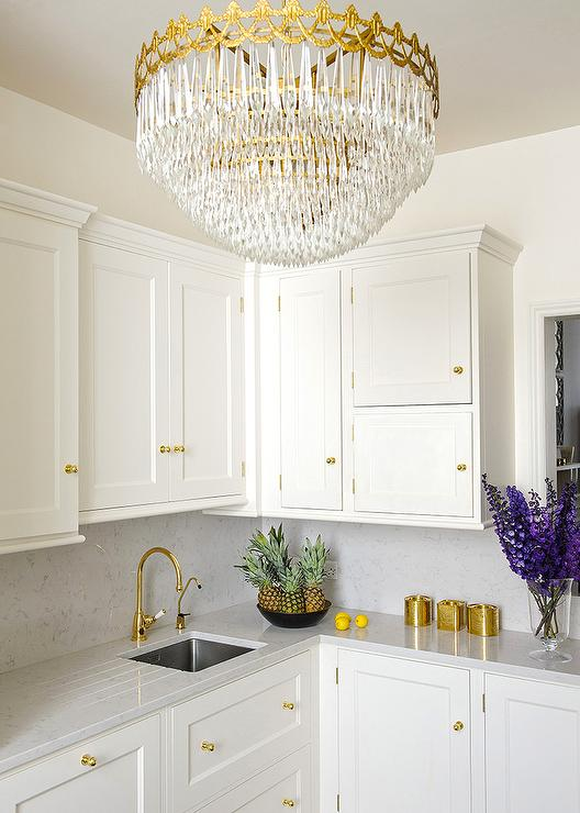 Exceptional White And Gold Kitchen Features White Shaker Cabinets Adorned With Polished Brass  Knobs Paired With White And Gray Quartz Countertops And Backsplash.