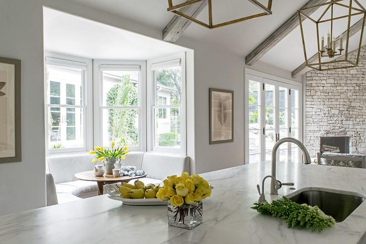 White Kitchen With Vaulted Ceiling Accented With Gray Wood