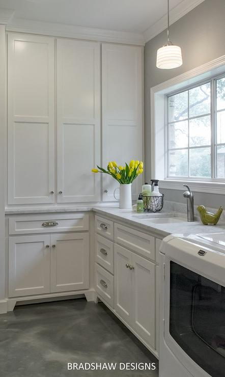 white and gray laundry room features white cabinets paired with gray and white marble countertops and backsplash