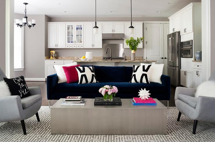 Contemporary Living Room Features A Dark Blue Velvet Sofa Lined With Black  And White Pillows Facing A Long Metal Cocktail Table Flanked By Gray Accent  ...