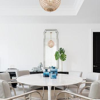 Round saarinen dining table lined with gray leather dining chairs
