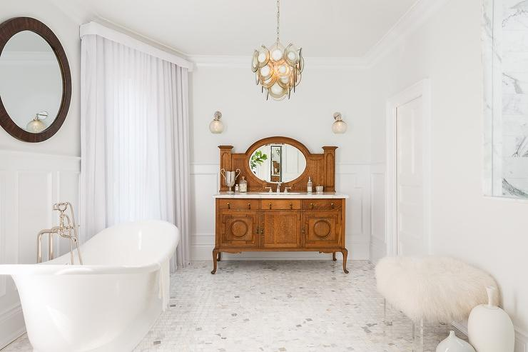 chic bathroom boasts upper walls painted pale gray and lower walls clad in wainscoting lined with a tub and vintage style tub filler under a