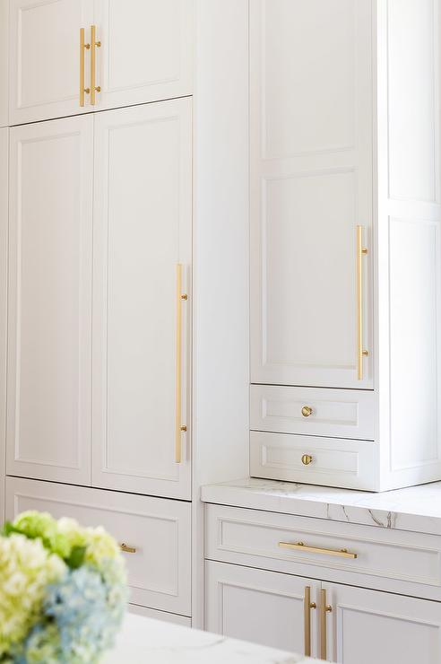 Alyssa rosenheck white kitchen cabinets with brass knobs for Long kitchen cupboard