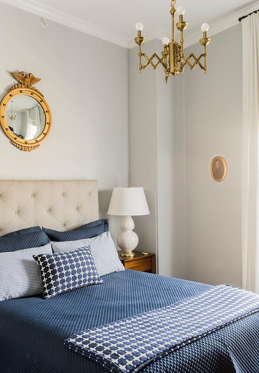 Gray And Gold Bedroom With Gold Mirror Over Headboard