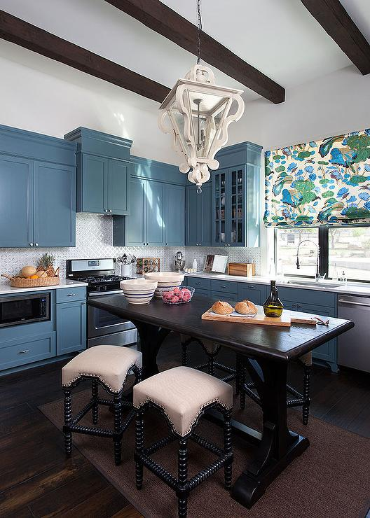 Amazing kitchen features blue shaker cabinets paired with white quartz