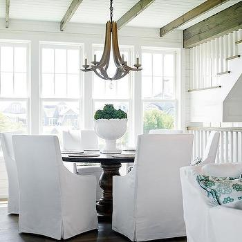 Beach Style Dining Room With Round Dining Table And White Slipcovered Chairs