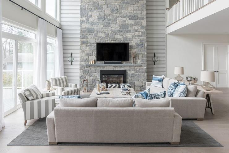 Blue And Gray Living Room With A Two Story Stone Fireplace Transitional