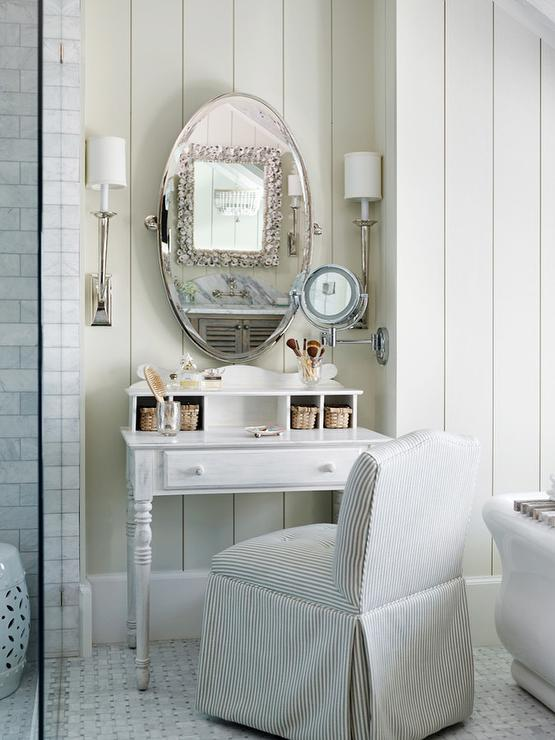 Chic Master Bath Features A Whitewashed Makeup Vanity With Turned Legs  Paired With A Gray Camelback Pinstripe Slipper Chair Placed Under An Oval  Pivot ...