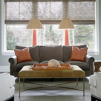 orange and gray living room features a gray velvet sofa lined with