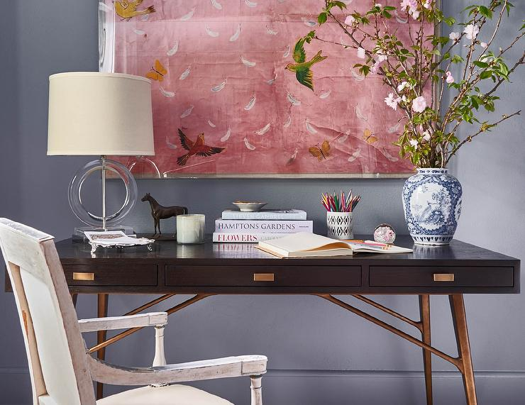 chic home office features a wall painted gray blue lined with a paule marrot feathers acrylic shadowbox framed print placed over a wood and brass desk with chic home office features