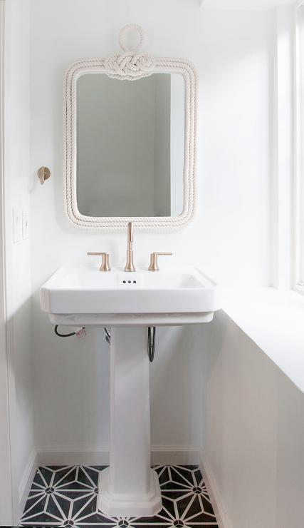 black and white cottage bathroom boasts a white rope mirror pottery barn belay white rope mirror placed above a white pedestal sink and satin nickel