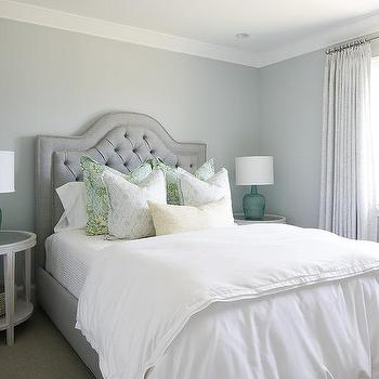 gray tufted bed with round whitewashed nightstands with mirror tops