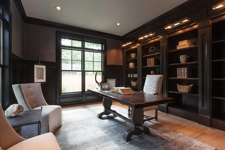 chic black paneled home office features a black trestle desk and a white and gray trellis fabric upholstered chair stands in front of a wall of floor to chic home office features