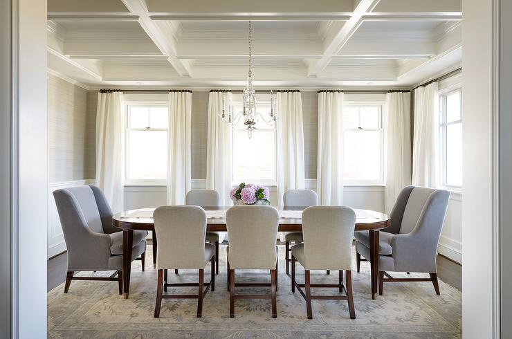 Of This Gorgeous Transitional Dining Room Featuring A Long Oval Wood Table Surrounded By Upholstered Light Gray Back Chairs And