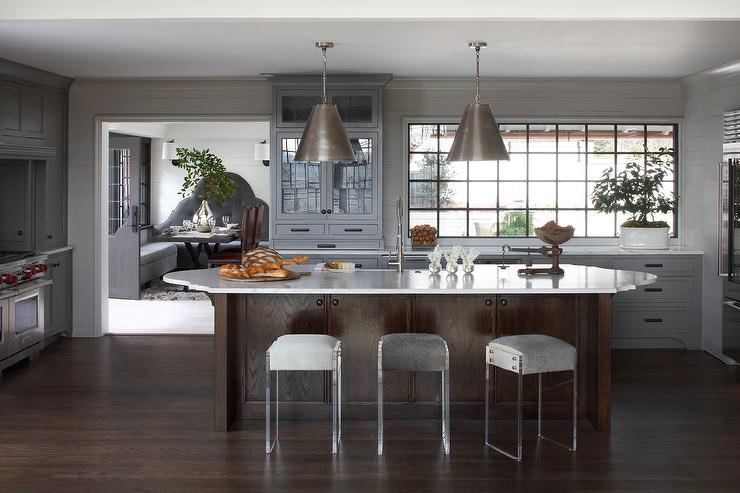 Dark Stained Kitchen Island With Oval Countertop And Backless Lucite Stools