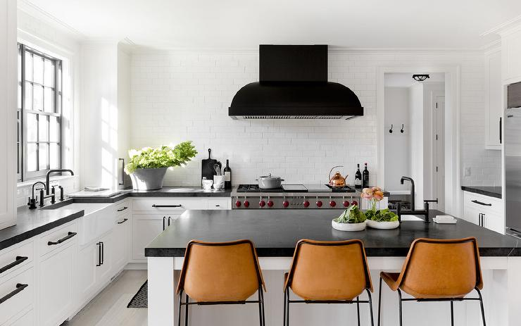 Black And White Kitchen With Orange Leather Barstools